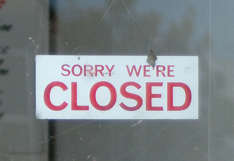 A closed sign hangs on a shop door obstr